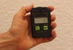 Carbon monoxide meter in hand.